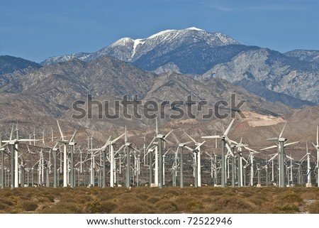 Wind Turbine farm located on California desert surrounded by mountains.