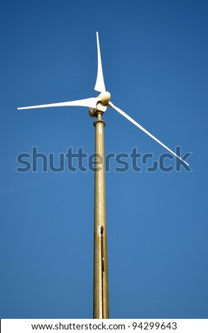 Wind turbine for sustainable energy production. Single windmill and blue sky