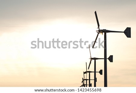 wind turbine generating electricity pole in row silhouette over clear golden sky #1423455698