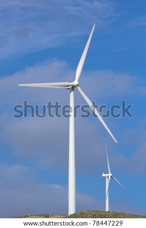 Wind turbine generating electricity with a nice white cloud on the sky