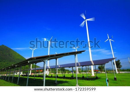 Wind turbine generator and solar energy panels with blue sky.