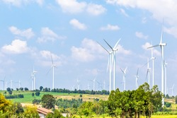 Wind turbine  generators line the hilltops and Aerial landscape with blue sky