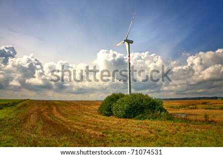 Wind turbine in an open field on cloudy day