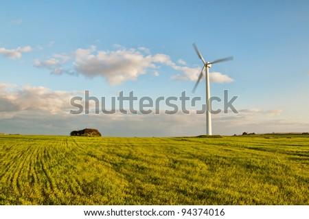 Wind turbine in green field - stock photo