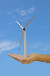 wind turbine in hand with blue sky-eco concept