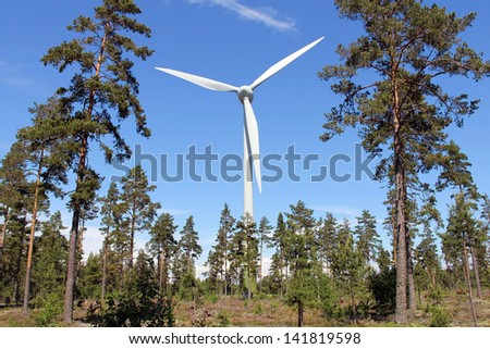 Wind turbine in pine forest near Hanko, Finland, on a bright day at summer.