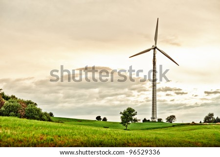 Wind Turbine in spring meadow at late afternoon