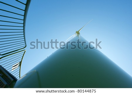 Wind turbine on a sunny summer afternoon.  Wide angle. - stock photo