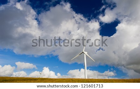 Wind turbine on the green grass over the deep blue clouded sky