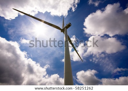 Wind turbine over a cloud filled blue sky, alternative energy source