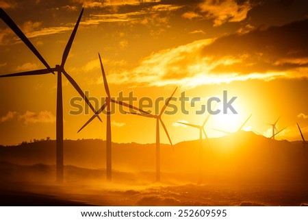 Wind turbine power generators silhouettes at ocean coastline at sunset. Alternative renewable energy production in Philippines