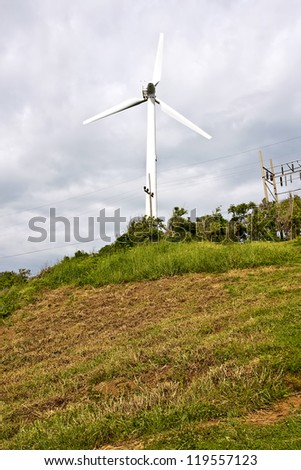 Wind turbine producing alternative energy with a cloudy sky