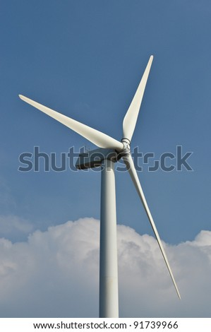 Wind turbine propeller blades against blue sky