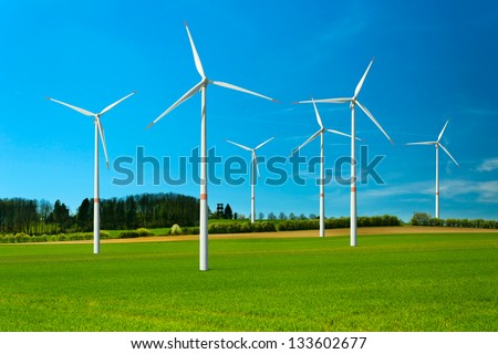 Wind turbine renewable energy source, summer landscape with clear blue sky and green field