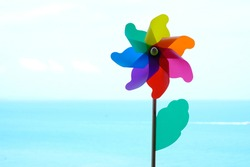 Wind turbine  with blue sea background.  Colorful pinwheel over blue sky background. Children`s colorful wind turbine toy. Green energy symbol.