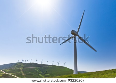 Wind turbine with more behind, horizontal, blade slightly motion blurred