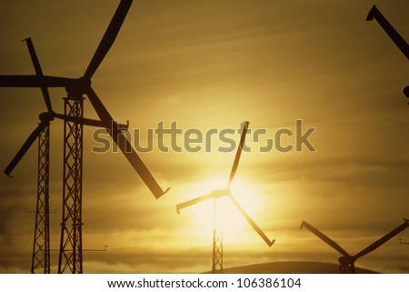 Wind turbines against golden sky
