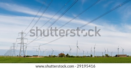 Wind turbines and Electricity Pylons in in a green field in East Sussex, England