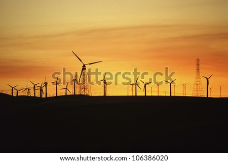Wind turbines and power lines against sunset