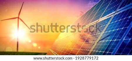 Wind Turbines And Solar Panels At Sunset - Renewable Energy Concept Foto stock ©