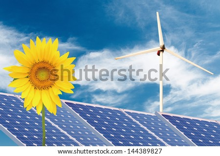 Wind turbines and solar panels on sunflowers field