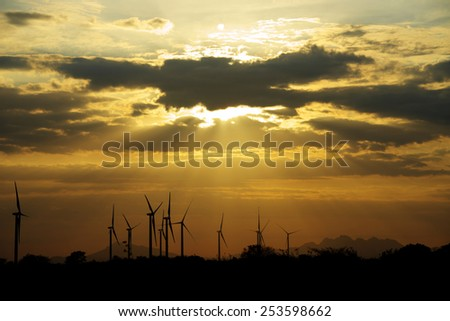 Wind turbines as silhouettes against a beautiful sunset with sun beams shining down