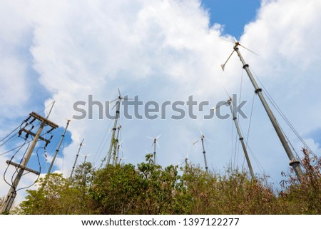Wind turbines farm and electric pole with blue sky. #1397122277