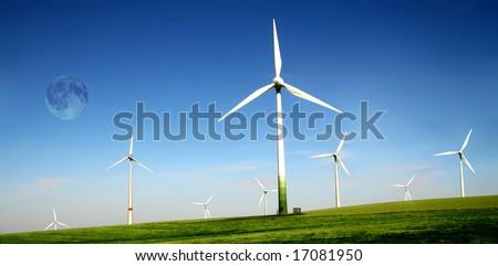 Wind turbines farm with full moon. Alternative energy source.