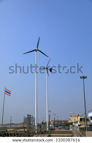 Wind turbines generating electricity for walkway with blue sky #1330387616