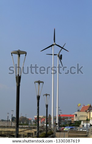 Wind turbines generating electricity for walkway with blue sky #1330387619