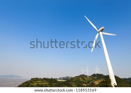 wind turbines generating electricity in wind farm at the beach