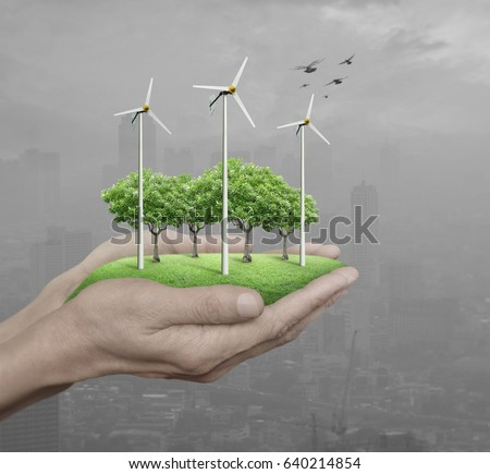 Wind turbines, grass and trees in human hands over pollution city, Ecological concept #640214854