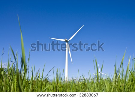 Wind turbines in a field. Modern day windmills producing green energy. - stock photo