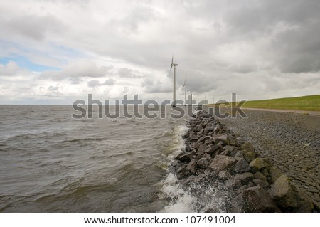 Wind turbines in a lake along a dike