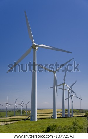 Wind turbines in a windfarm against a blue sky