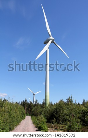 Wind turbines in forest against blue sky at summer. Photographed near Hanko, Finland.