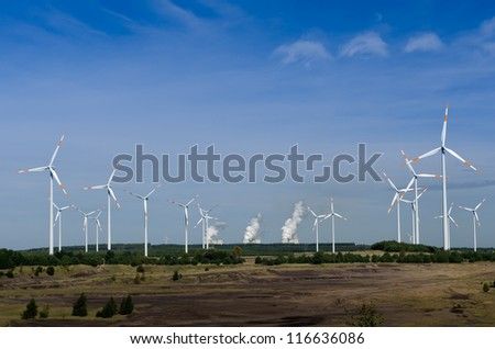 Wind turbines in front of a coal-fired plant