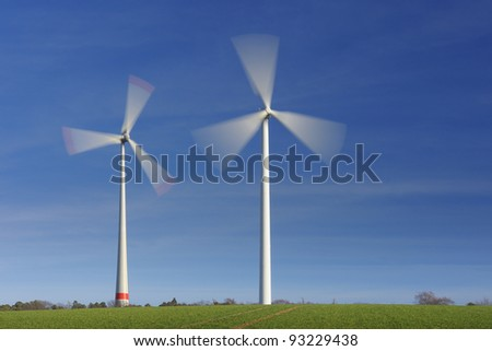 Wind turbines in movement against blue sky