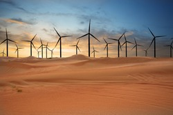 Wind turbines in the desert suggesting renewable energy concept with sand dunes at sunset