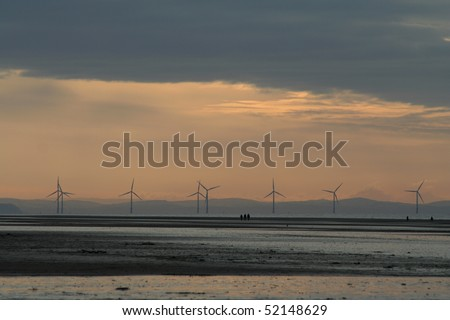 Wind Turbines in the Mersey Estuary at Sunset. People walk across the sands.