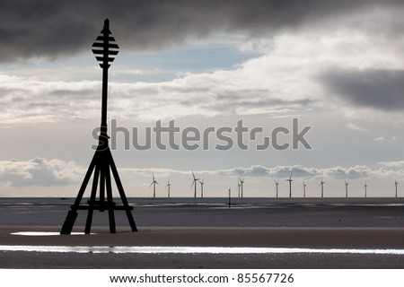 Wind turbines in the ocean off a sandy beach near Liverpool on a cold and cloudy day - stock photo