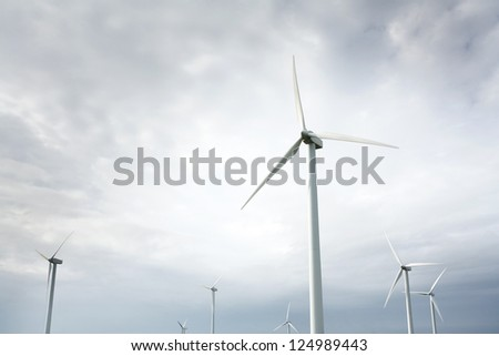 Wind Turbines in wind farm against cloudy sky - stock photo