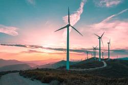 Wind turbines on beautiful sunny summer purple autumn mountain landsape. Curvy road through mountain Eolic park. Green ecological power energy generation. Wind farm eco field