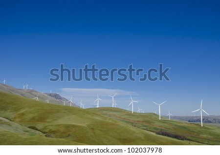 Wind turbines on green hills under a blue sky