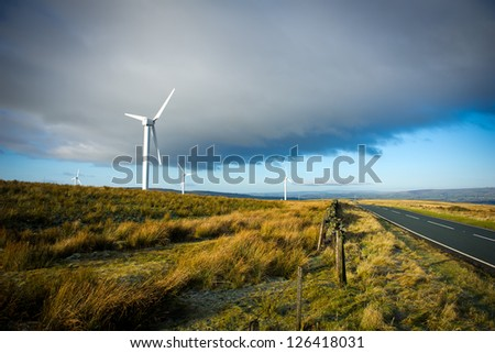 Wind turbines on the green grass over the blue clouded sky