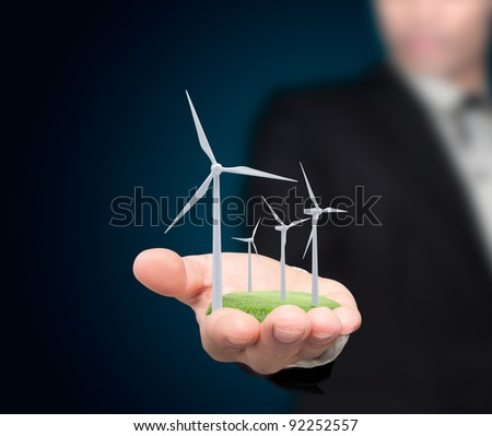 Wind turbines on the hands businessman.