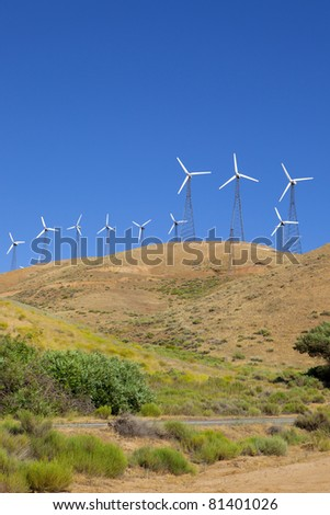 Wind turbines on top of a hillside.