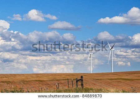 Wind turbines stand like friendly giants on the horizon against a beautiful blue and cloudy sky