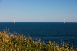Wind turbines stand off the shores of Block Island, Rhode Island, USA.
