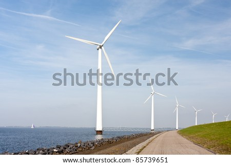 Wind turbines standing along the dyke in the Dutch sea